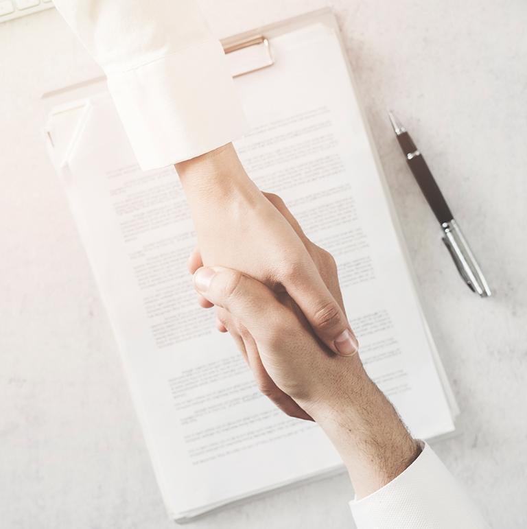 Uściśnięte dłonie na tle dokumentacji prawnej